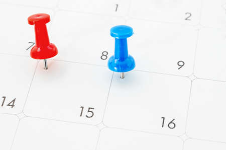 Red and blue pin on White Calendar Closeup shot ready for text or message.