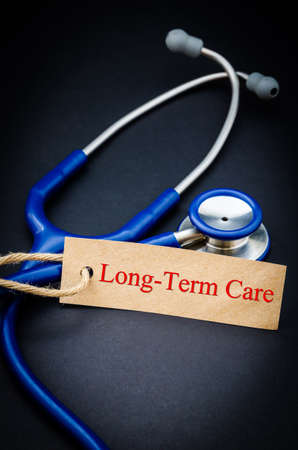 long term: Long term care in paper tag with stethoscope on black background Stock Photo