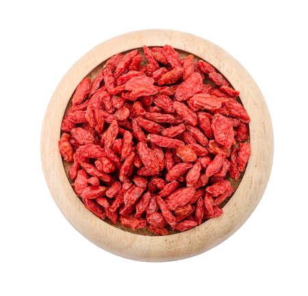 Dried Tibetan goji berries (wolfberry) in wooden dish isolated on white background