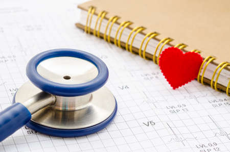 Medical stethoscope and red heart lying with diary on cardiogram chart closeup.