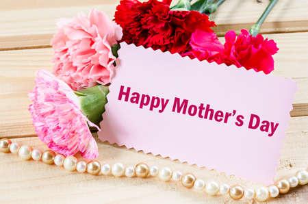 agradecimiento: mensaje del día de madres con claveles de color rosa sobre fondo de madera.
