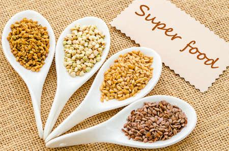 fenugreek: Super food tag with fenugreek seeds, bukwheat seeds, gold linseeds and brown linseeds.