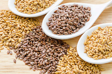 Brown and gold linseeds or flaxseeds difference on wooden background. Stock Photo