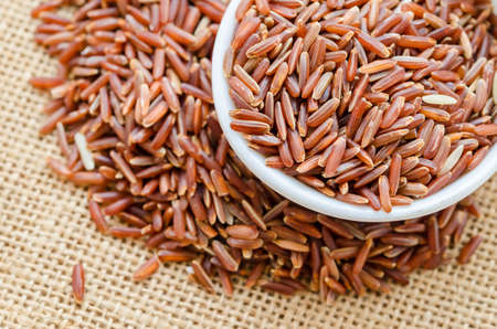 processed grains: Red rice in white bowl on sack background.