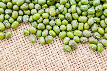 Mung bean seeds on sack background.