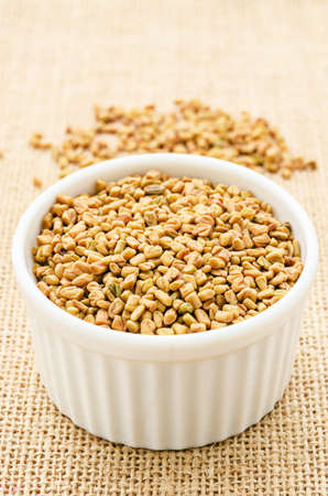 Fenugreek seeds in white bowl on sack background.