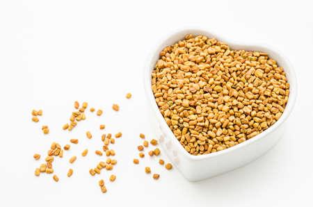 methi: Fenugreek seeds in white bowl on white background Stock Photo