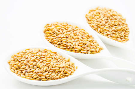 Golden flax seeds or linseeds in white spoon on white background. Super food. Imagens