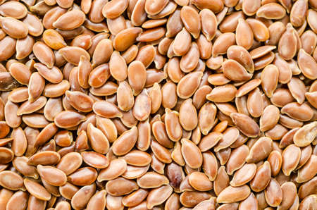Brown flax seed background. Flax seed is a good source of omega-3 fatty acids, can aid in digestion, and is used to make linseed oil. The plants are used to make linen.