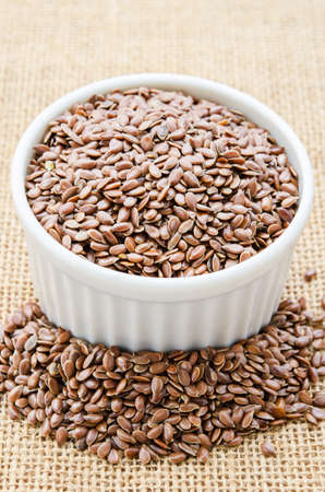 brown flax: Brown flax seeds or linseeds in white bowl on sack background.