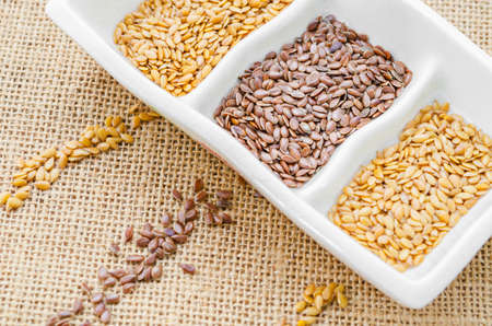 gold flax: Difference of gold and brown linseeds or flax seeds in white bowl on sack background.