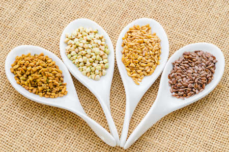 fenugreek: fenugreek seeds, bukwheat seeds, gold linseeds and brown linseeds in white spoon on sack background. Stock Photo
