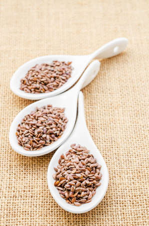 brown flax: Brown flax seeds or linseed in white spoons on sack background. Stock Photo