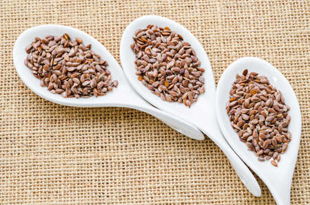 brown flax: Brown flax seeds or linseed in white spoon on sack background. Stock Photo