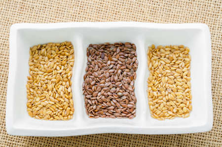 lipoprotein: Difference of Golden linseeds and brown linseeds (flax seeds) in white cup on sack background.