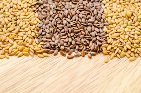 gold flax: Difference of Golden linseeds and brown linseeds (flax seeds) on wooden background.