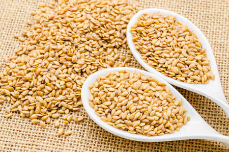 flax seeds: Gold flax seeds or Linseed in white spoon on sack background.