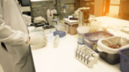 Out of focus young researcher works in chemistry laboratory as background.