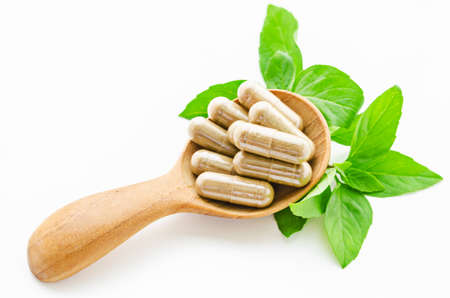 Herbal medicine capsules in wooden spoon with green leaves on white background.