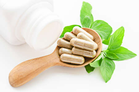 herbal background: Herbal medicine capsules in wooden spoon with green leaves on white background.