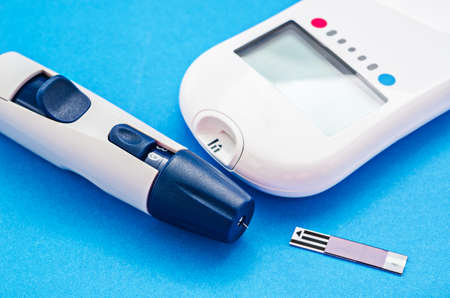 blood glucose meter on blue background.