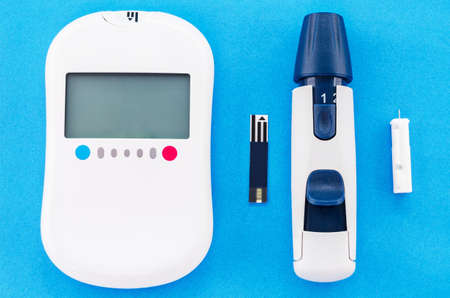 drug control: blood glucose meter and equipment on blue background.