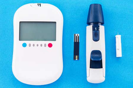 dedo indice: medidor de glucosa en la sangre y el equipo en el fondo azul.