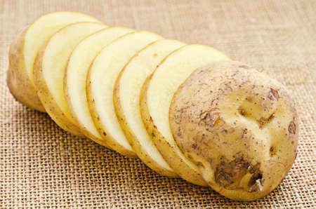 Fresh Potato slices on sack background.