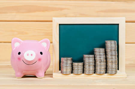 blank chalkboard: Pink piggy save money and coin in blank chalkboard on wooden room.