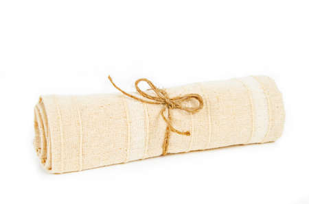 fabric roll: Roll of vintage tablecloth fabric with rope on white background.