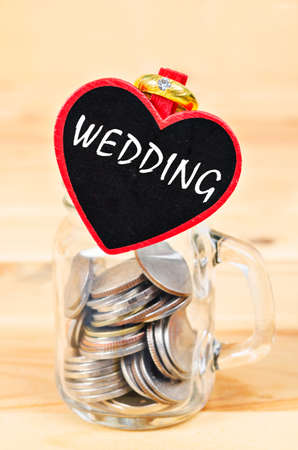 Savings in glass bank and Wedding Ring on wooden background.