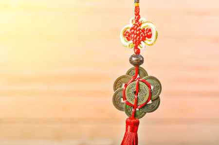 ascendant: chinese coins of luck holding on wooden background.