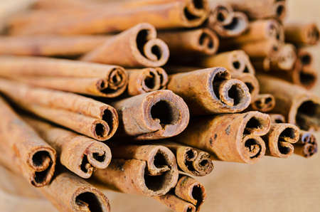 ingradient: Cinnamon sticks in cup on wooden background. Stock Photo