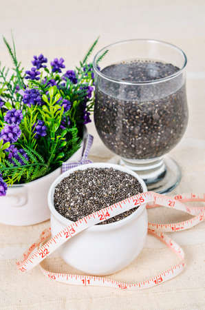 soak: Healthy Chia seeds in white cup and soak in water with measuring tape on tablecloth.