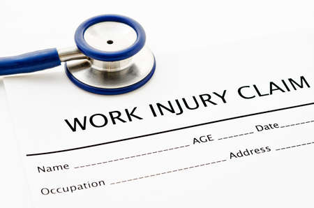 compensate: Claim form for an injury with stethoscope on white background.