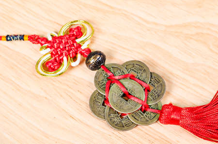 monete antiche: Lucky knot for Chinese new year greeting on wooden background. Archivio Fotografico