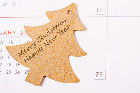 marked boxes: Merry christmas and happy new year on christmas tree card on close up at date 25th calendar page Stock Photo