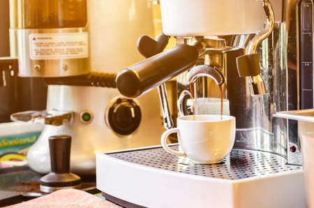 Close-up of espresso pouring from coffee machine with lighting.