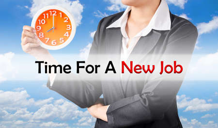 looking for job: Time for a new job, and business woman holding clock on blue sky background. Business concept. Stock Photo