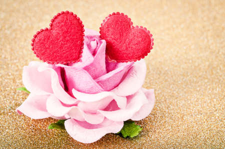 Pink rose with two red heart on golden glitter background. Stock Photo