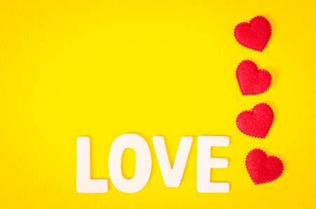 top veiw: Love word and red heart with empty space on yellow background.