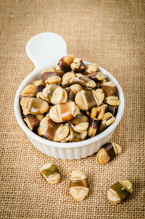 Roasted broad beans with salted in white cup on sack background.