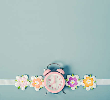 Pink alarm clock and colorful flower with empty space for background.