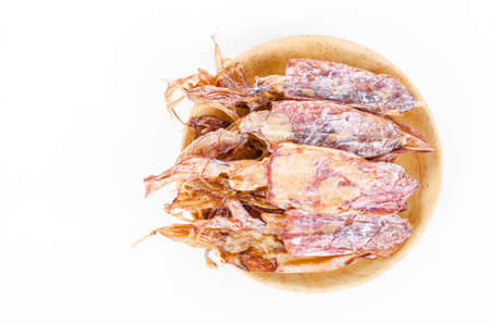 Dried squid in wooden dish on white background.