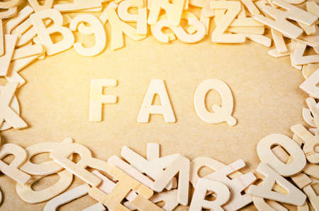 Wood letters as FAQ abbreviation, frequently asked questions on wooden background. Stock Photo