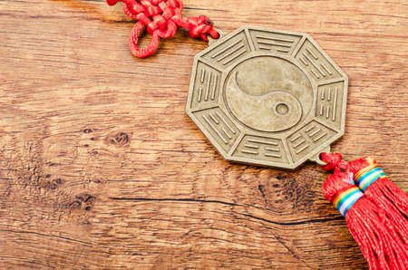 Close up metal sign of Yin Yang coin on wooden background