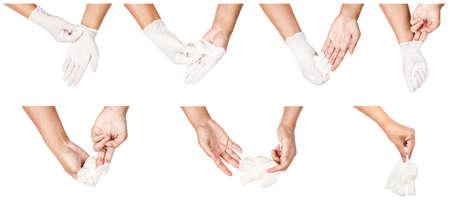 Paso de la mano tirando guantes desechables blancos médicos, aislado sobre fondo blanco. Concepto de control de la infección. Foto de archivo