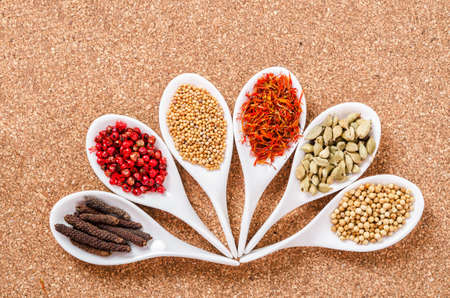 various spices and herbs on wooden background.