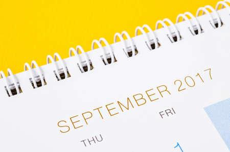 September on white calendar page, desk calendar on yellow background
