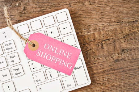 e commerce icon: Online shoping tag price on white keyboard on wooden background with free space. Stock Photo